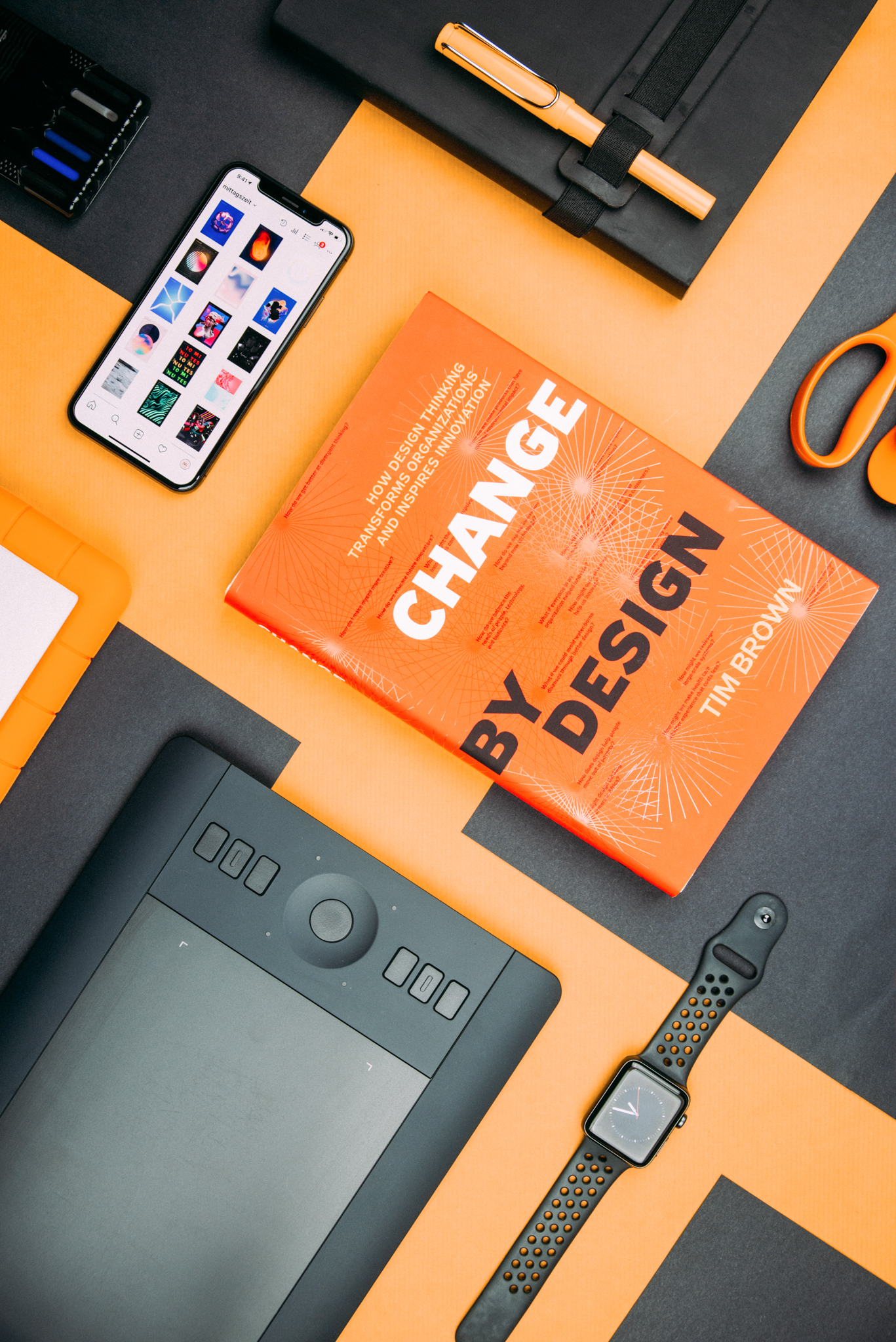 Top down shot of desk with the book change by design centred, other objects include phone, graphics pad, notepad and scissors