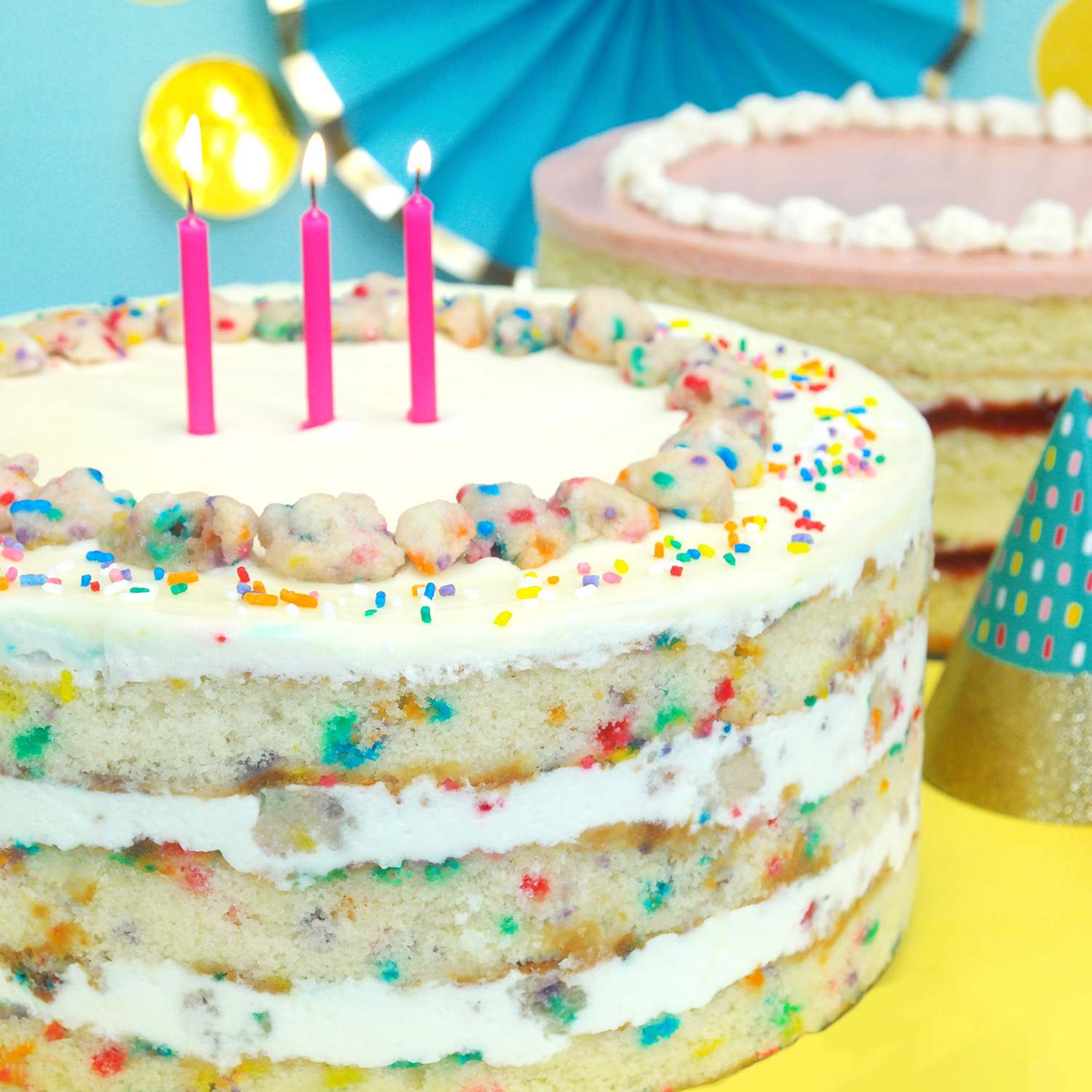 milk bar birthday cake with pink candles and sprinkles