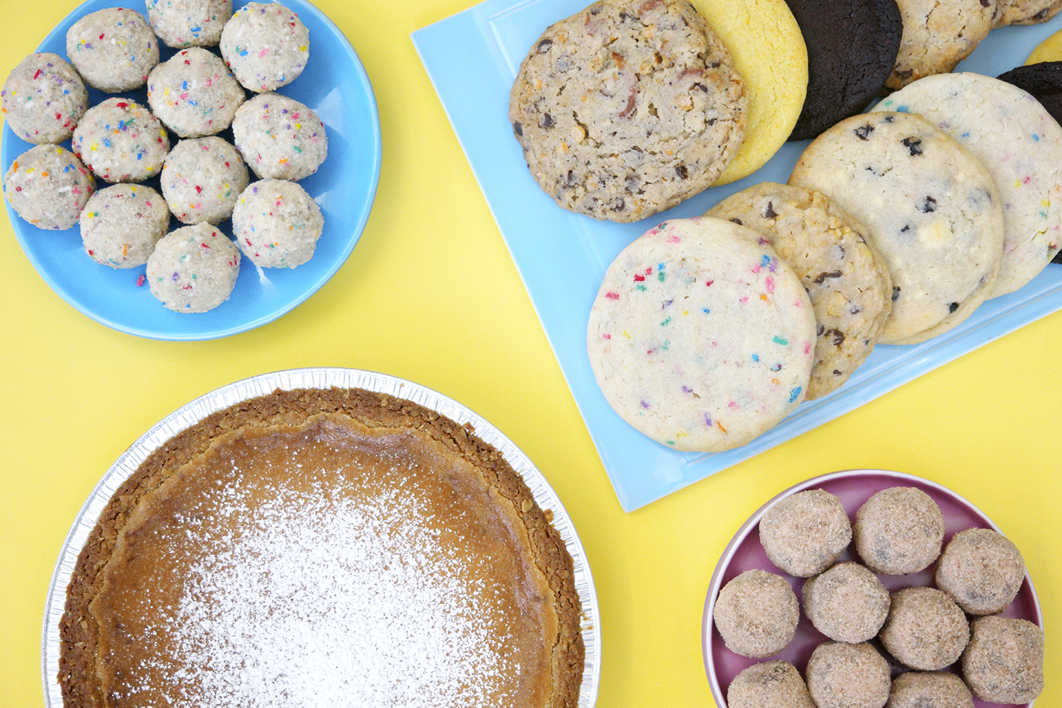 milk bar pie cookies and cake truffles on yellow background in flat lay style