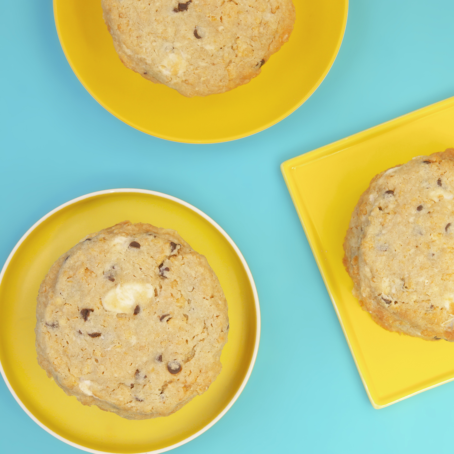 three chocolate chip cookies on yellow plates