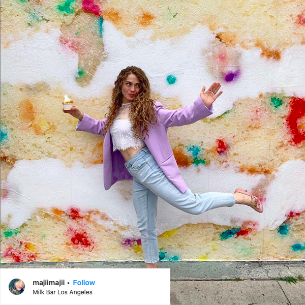 Instagram Post of a woman in front of the cake mural