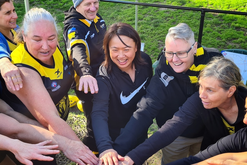 Sarah Loh and other team players place their hands in together on a football field.