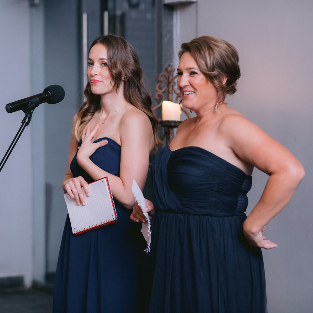 Two beautiful women speaking on a microphone in Groot Constantia, supplied by Western Cape DJs, The DJ Company.