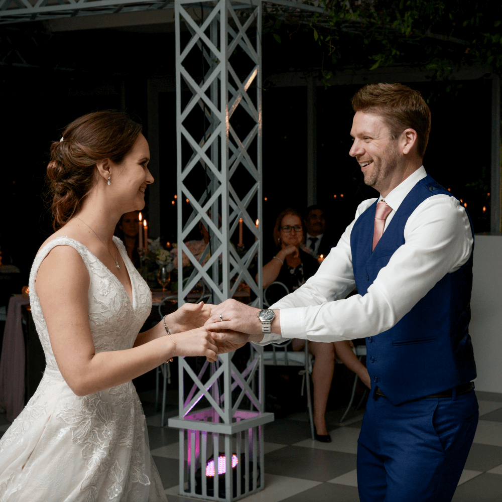 A couple smiling and dancing to the South African DJ's music at their wedding.