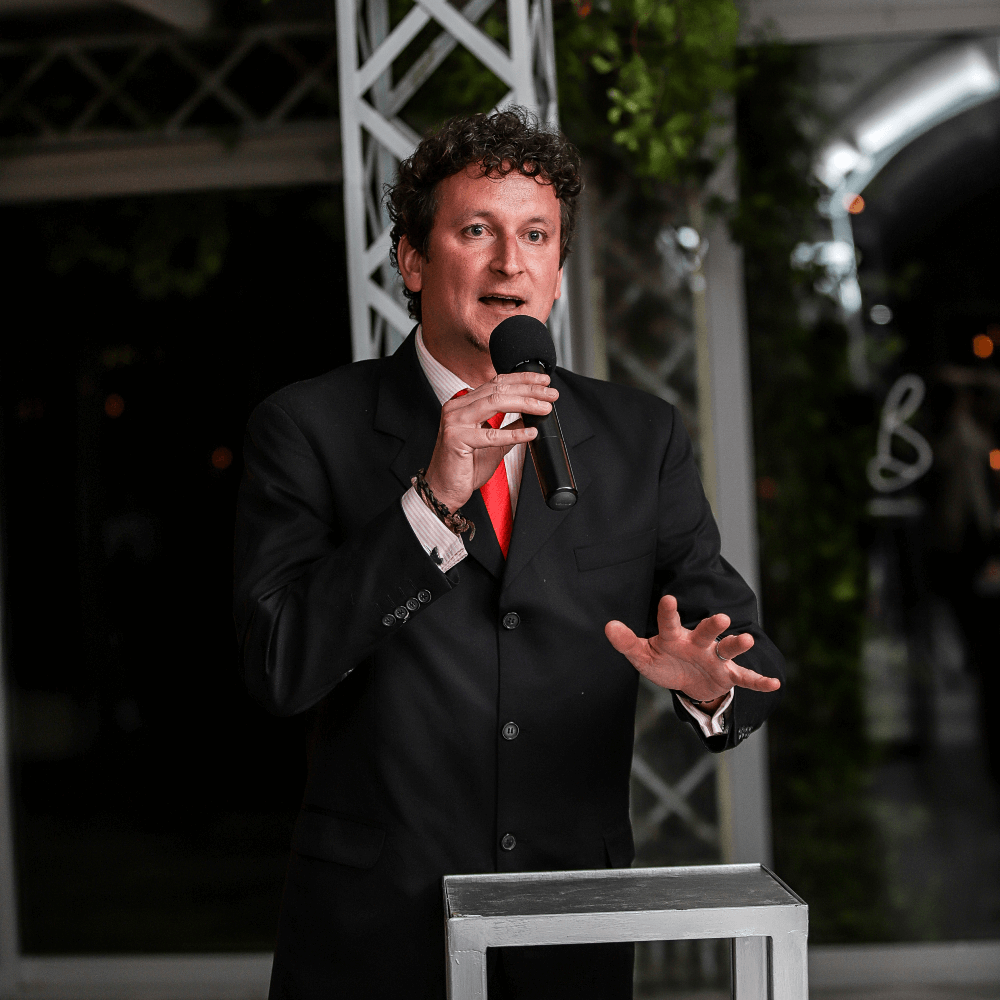 A man in a suit with a red tie saying a speech at a corporate function on a DJ Company microphone.