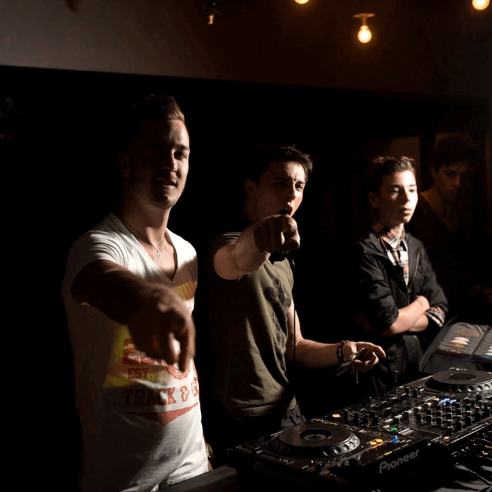 Three club DJs from South Africa pointing their fingers at the camera and screaming.