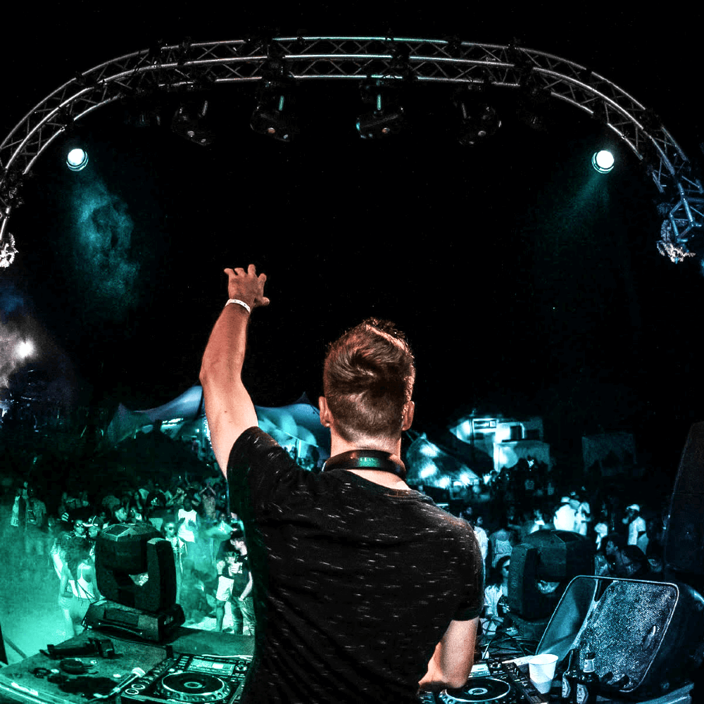 A festival DJ from Cape Town, Western Cape holding his hand up to a massive crowd.