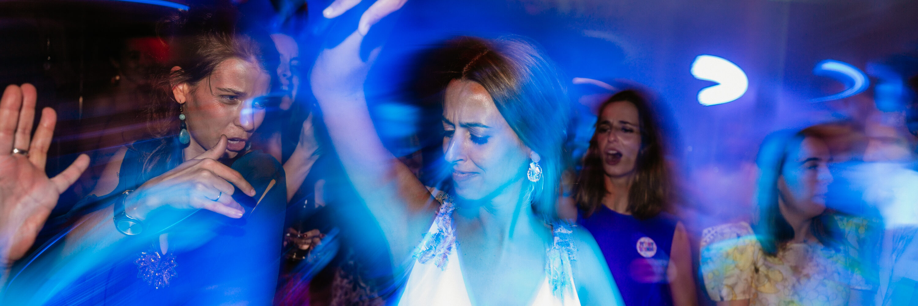 A bride and her friends dancing in beautiful diamond lighting.