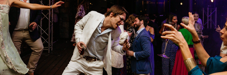 A man dressed like Elvis Presley dancing at an upmarket event.