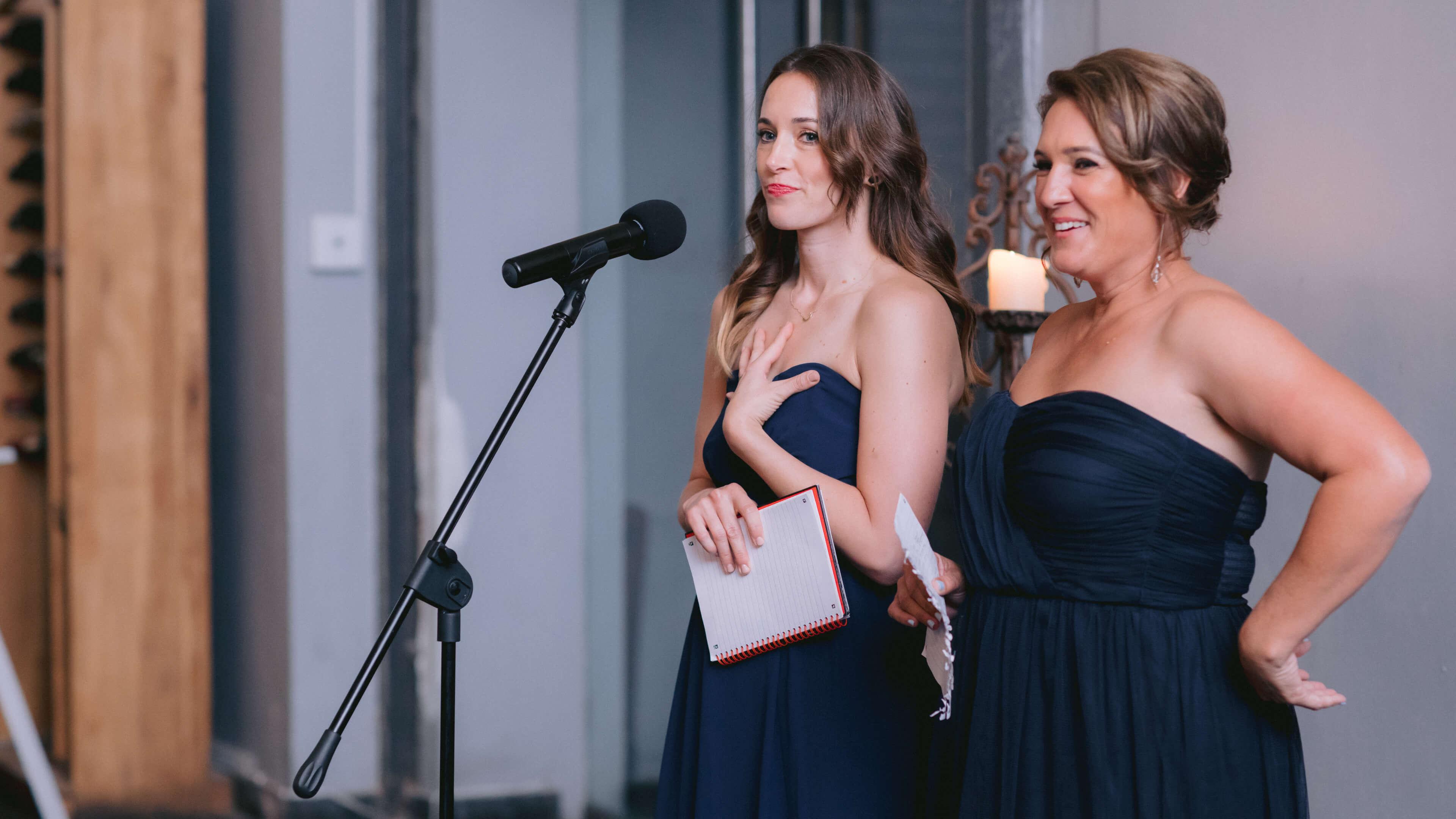 Two beautiful women speaking on a Shure microphone.
