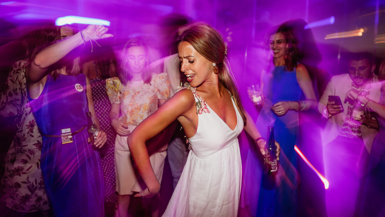 A woman dancing in purple light.