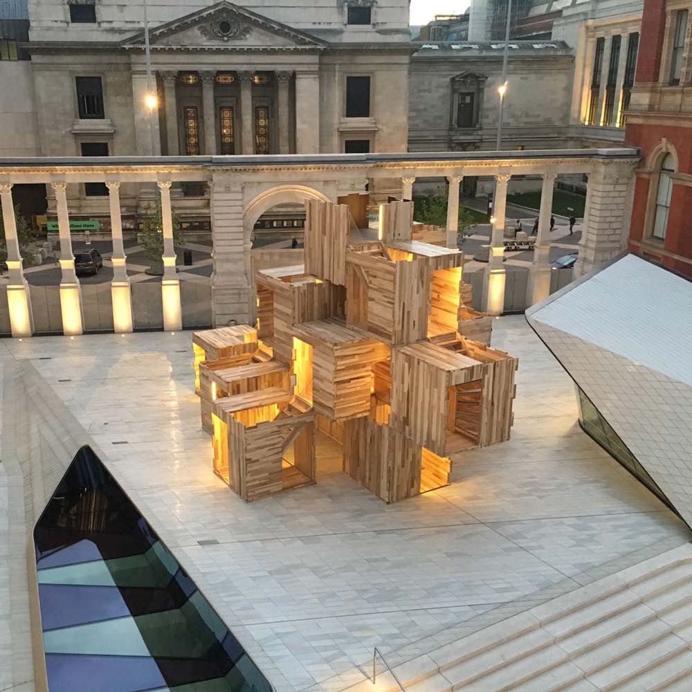 Evening photograph of a re-configurable modular timber pavilion, Multiply, at the Sackler courtyard, V&A museum