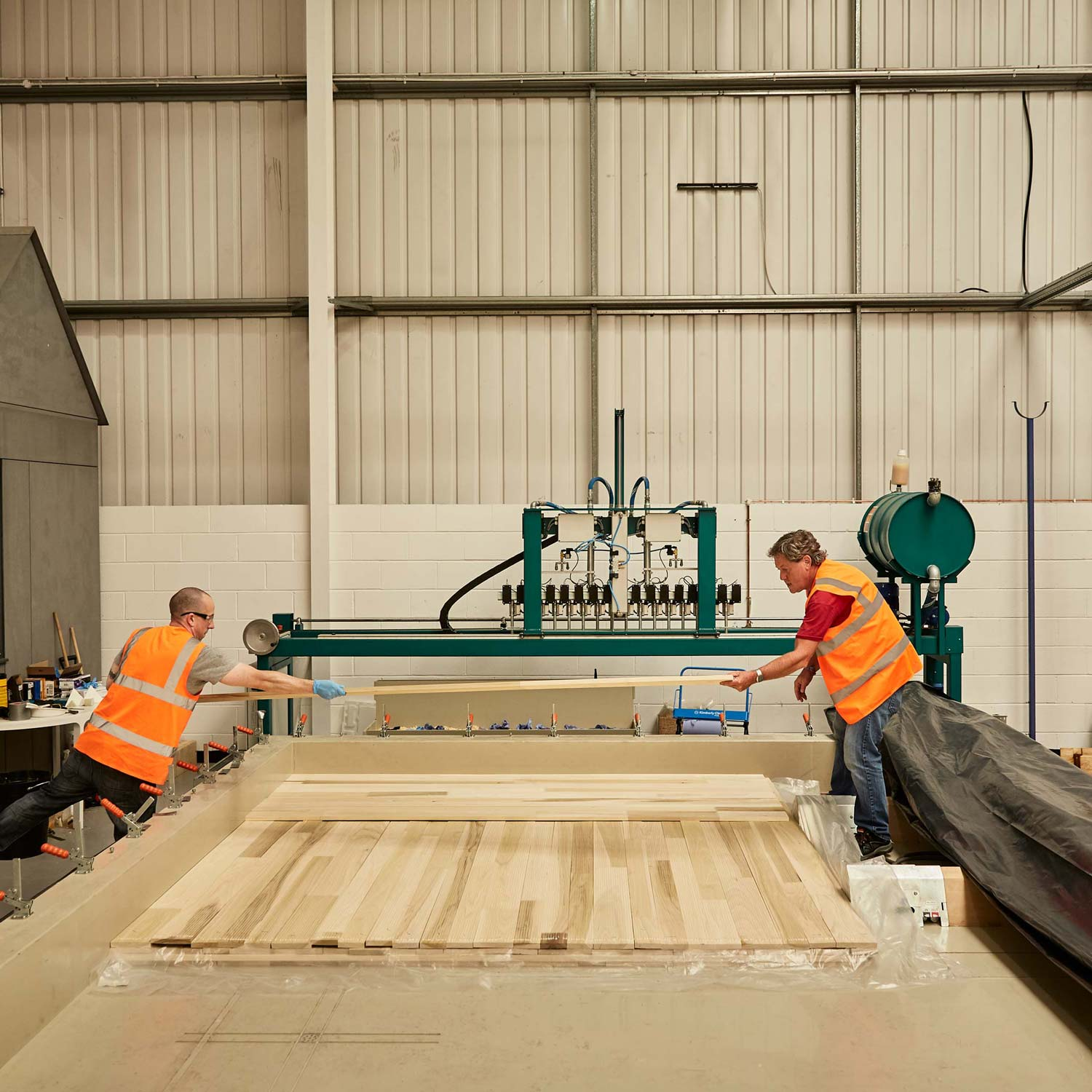 Two woodworkers constructing cross laminated timber sheets in the workshop