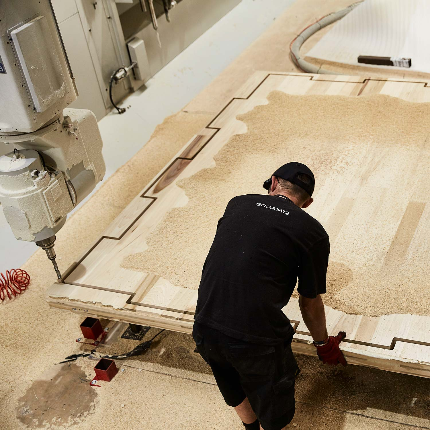 A worker fabricating a sheet of timber in the workshop through parametric design