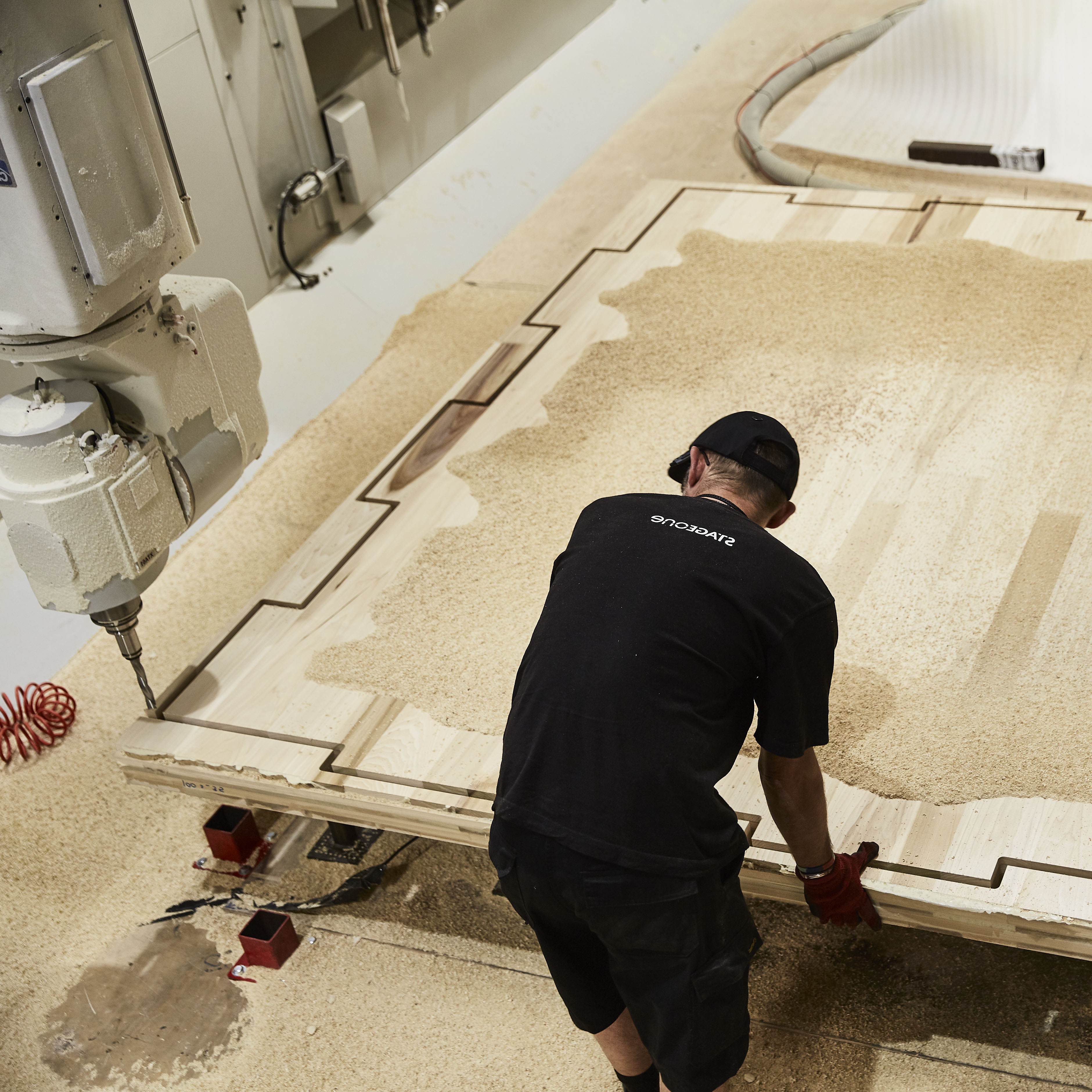 High fidelity photo of a worker fabricating a sheet of timber in the workshop through parametric design