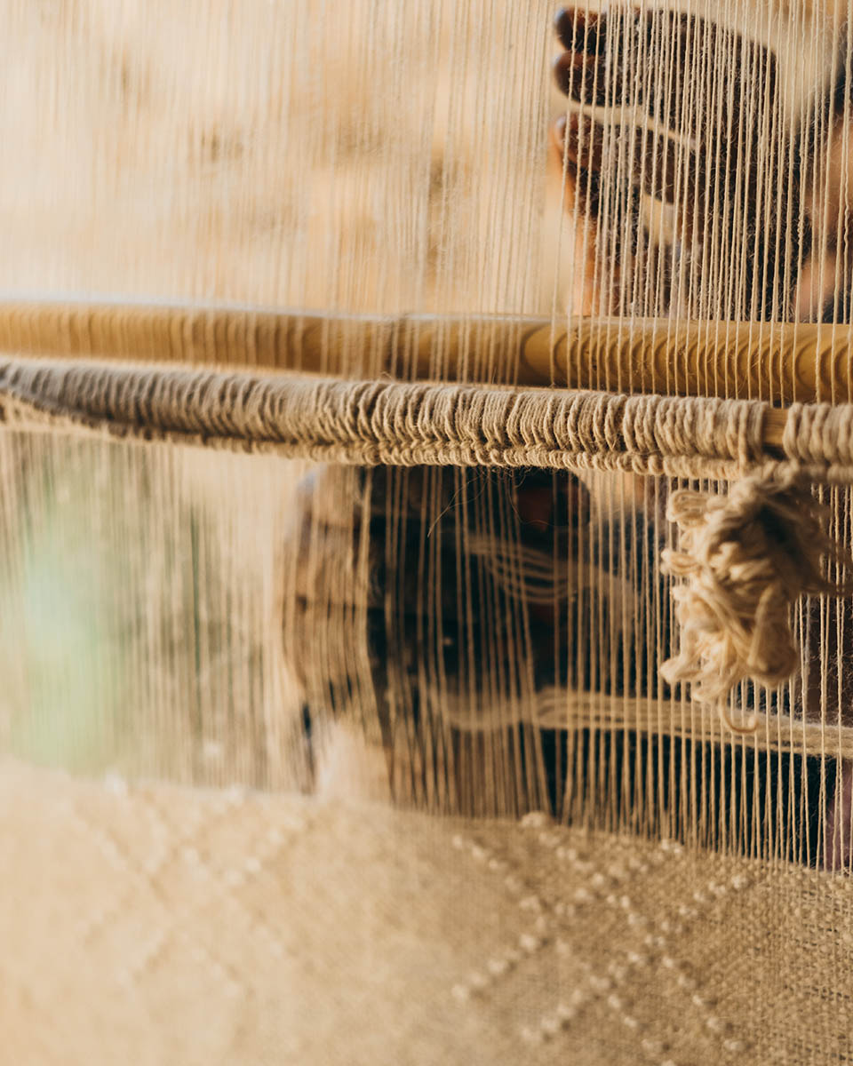 A woman weaver weaving a wool and cotton fabric on a vertical loom