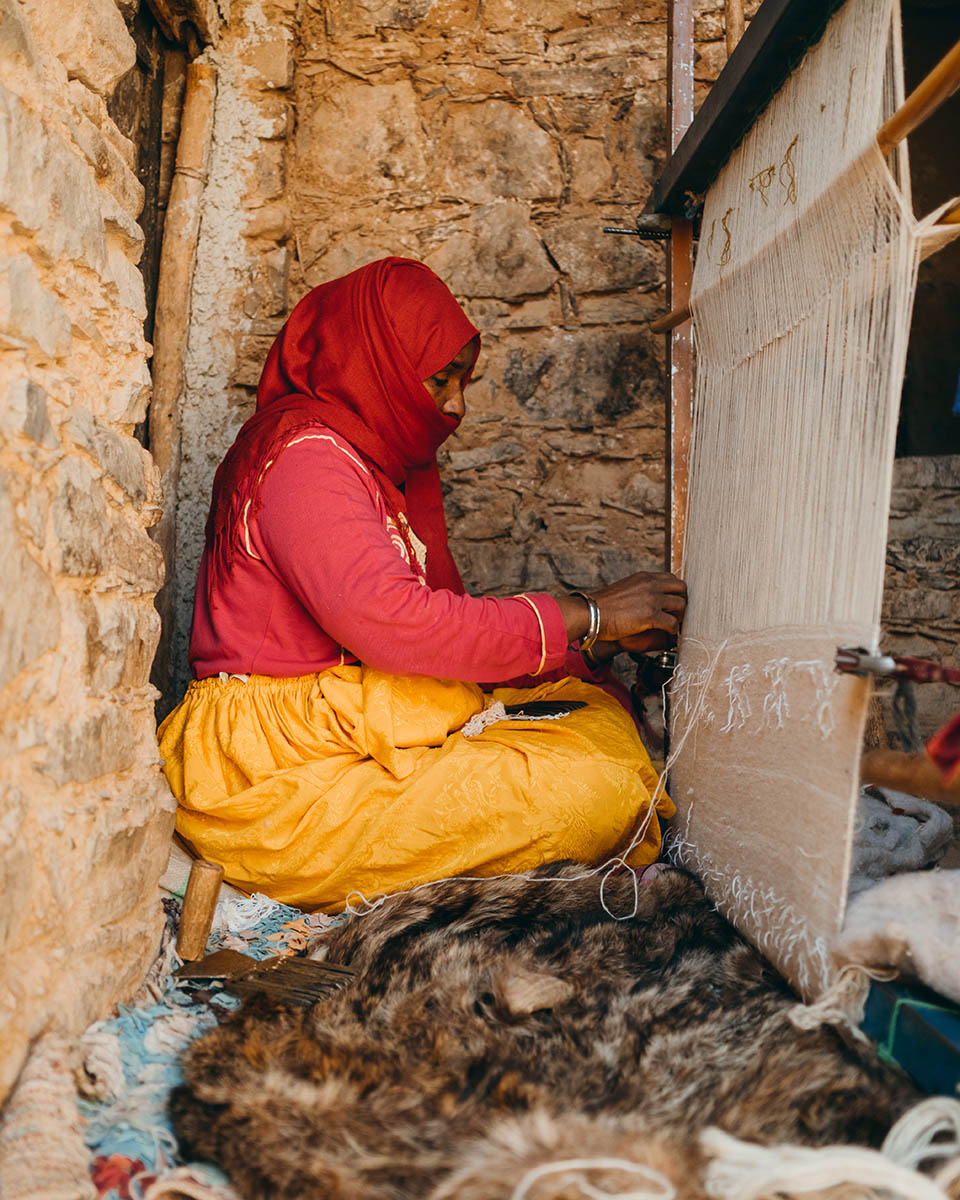 A Moroccan weaver weaving a wool and cotton fabric on a vertical loom