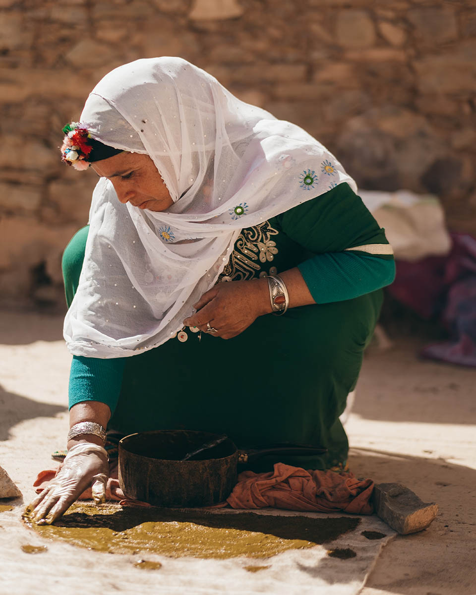 A Moroccan weaver paints a wool fabric by hand with henna paste