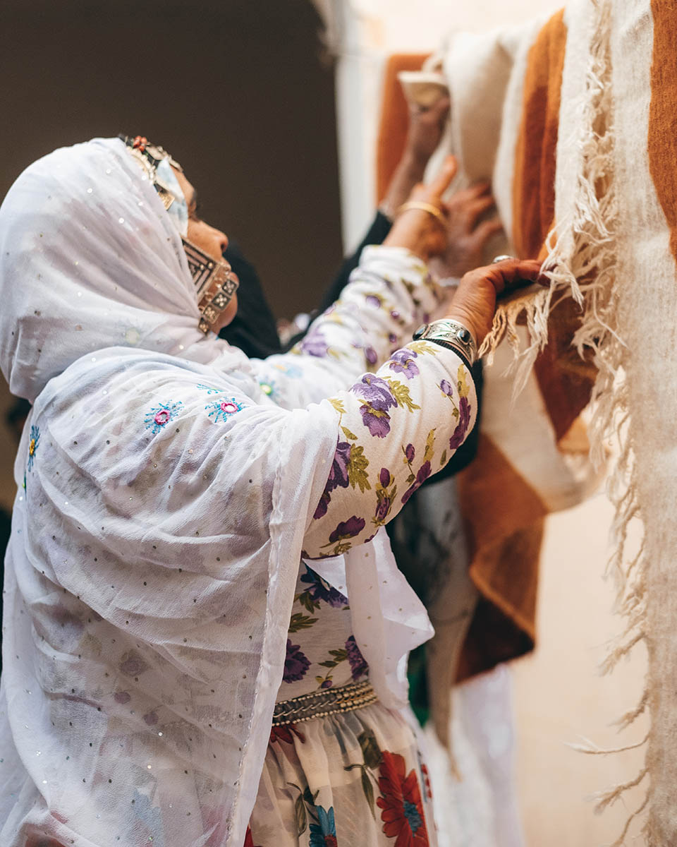 A woman weaver from the Anti Atlas hangs some wool fabrics decorated with henna