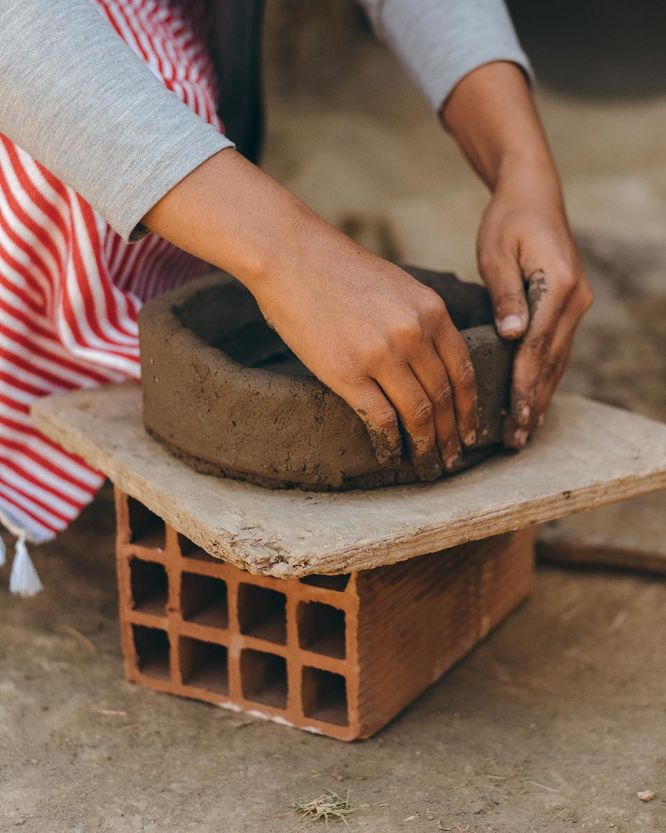 A woman potter builds by hand a traditionnal plate
