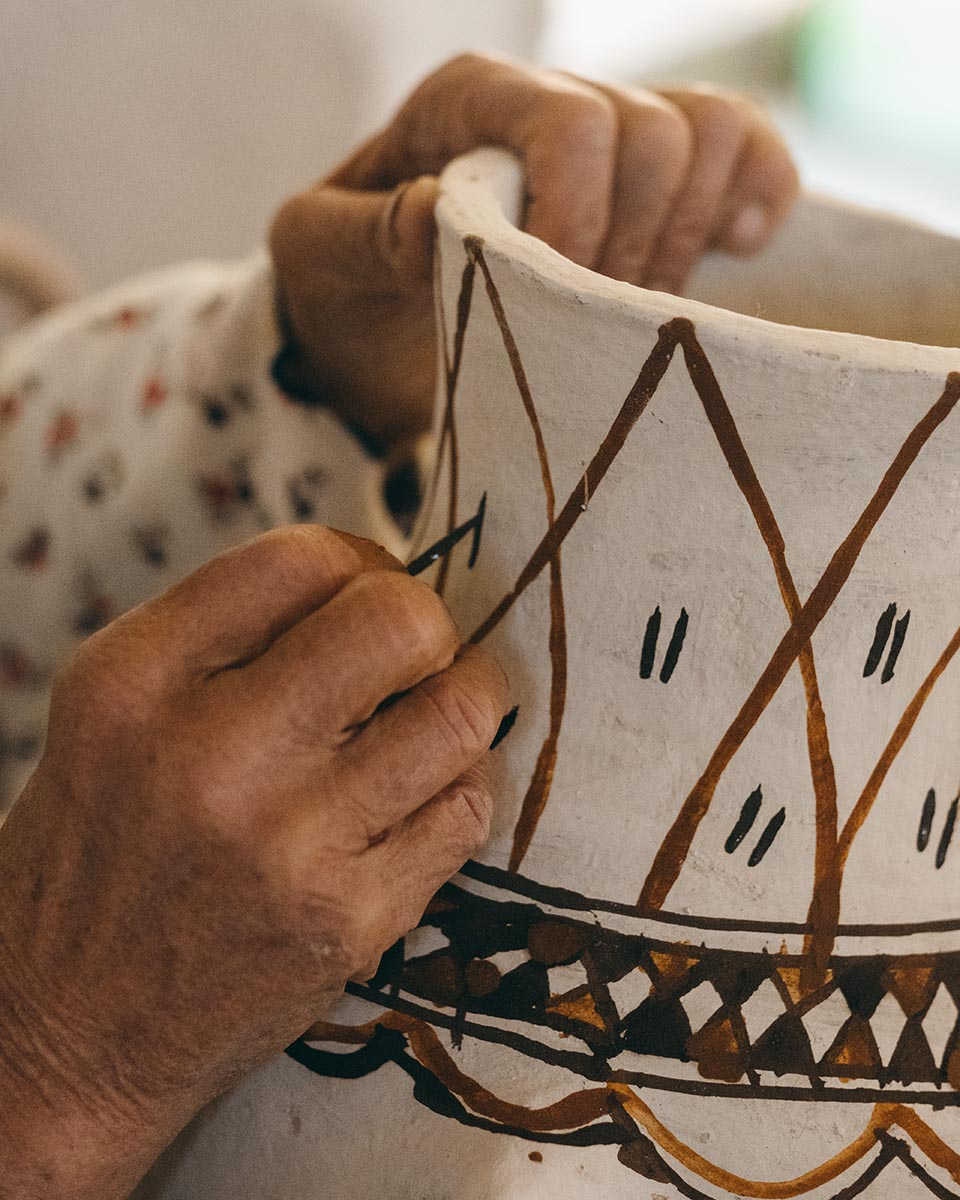 A potter from the Rif paints her tribe symbols on a traditionnal jar