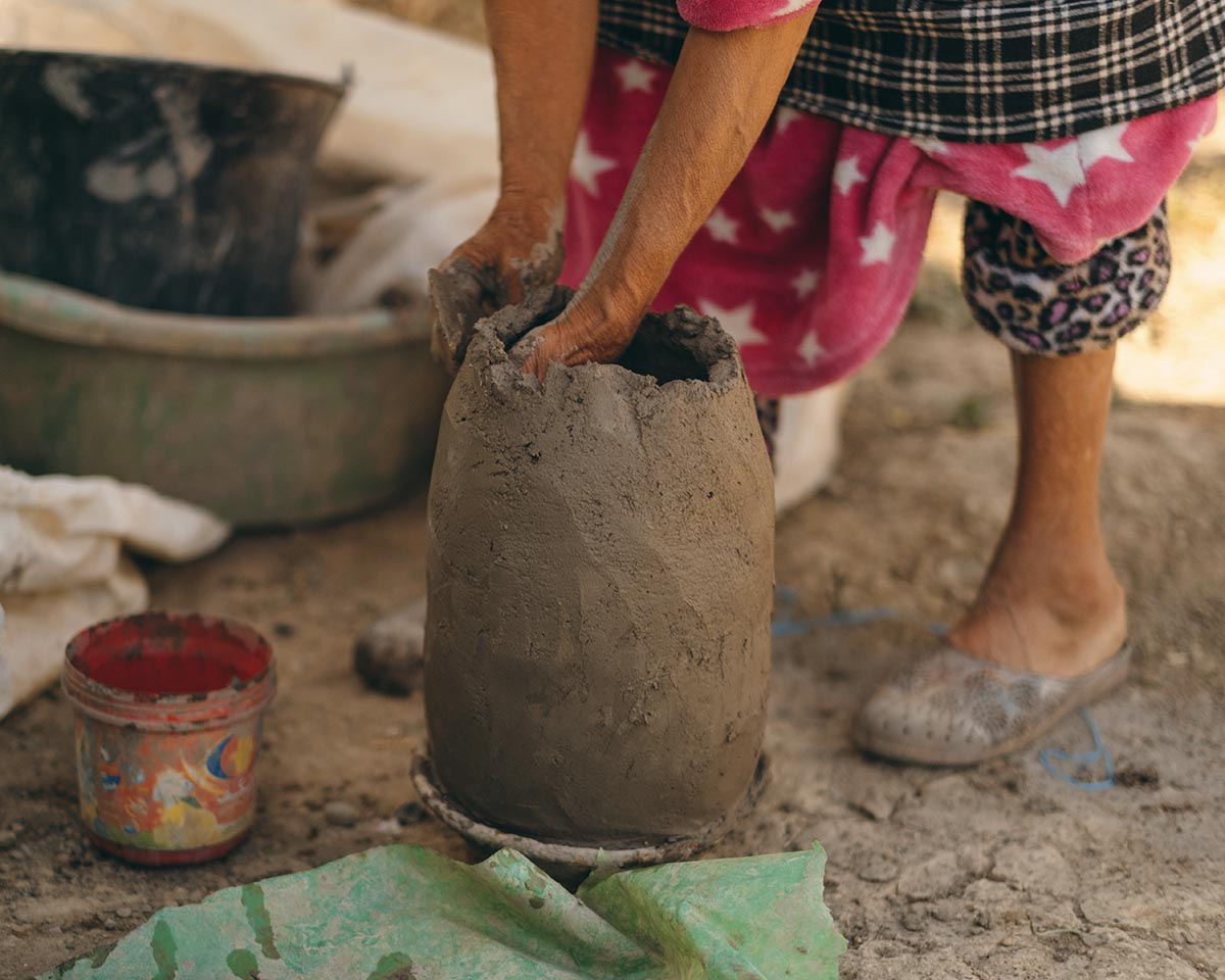 A Moroccan woman potter from the Rif region builds a traditional churn.