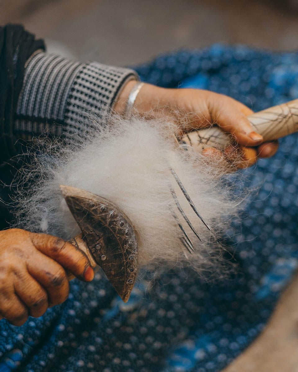 A woman weaver from the Anti Atlas cards the raw wool.