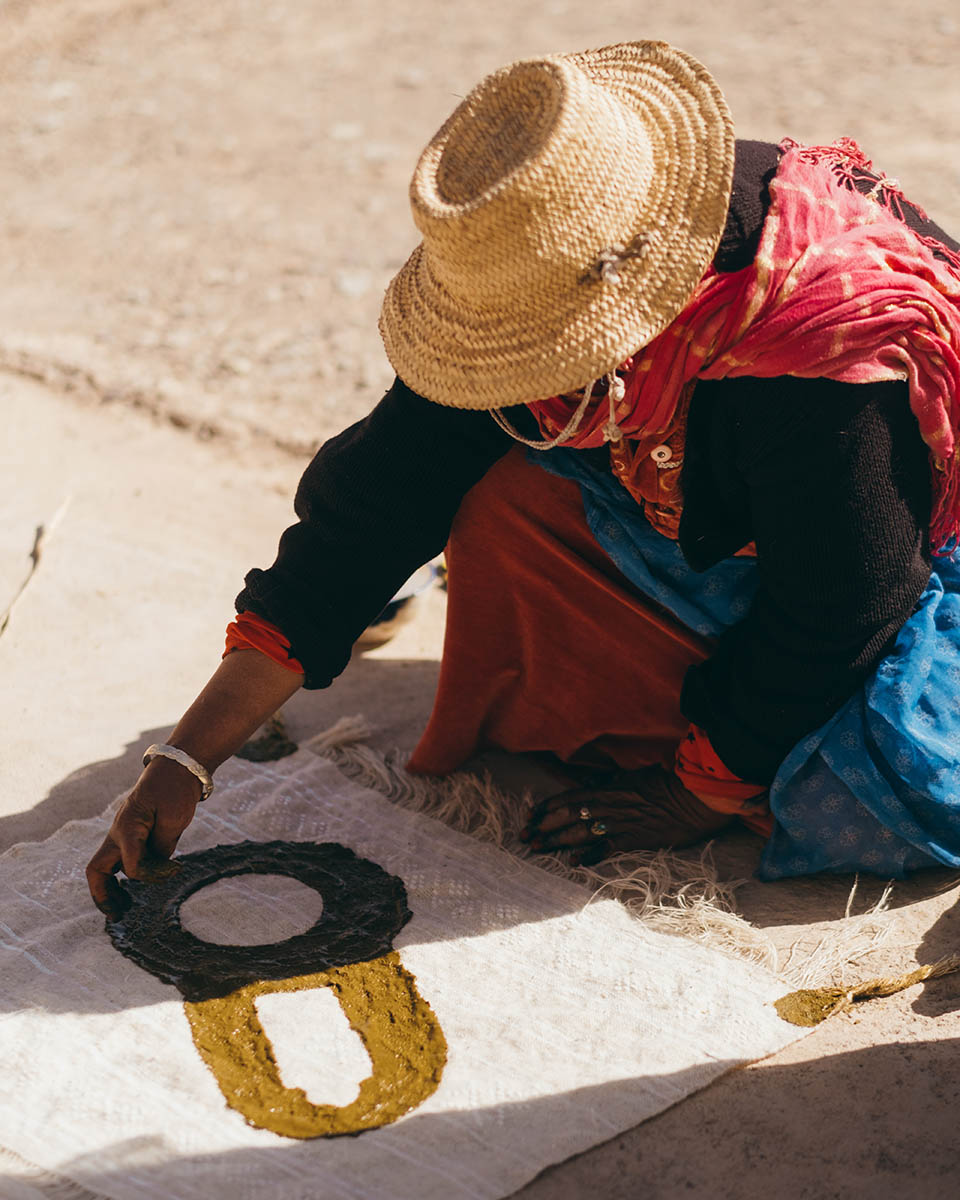 A woman weaver from the Anti Atlas paints a wool fabric with henna paste.