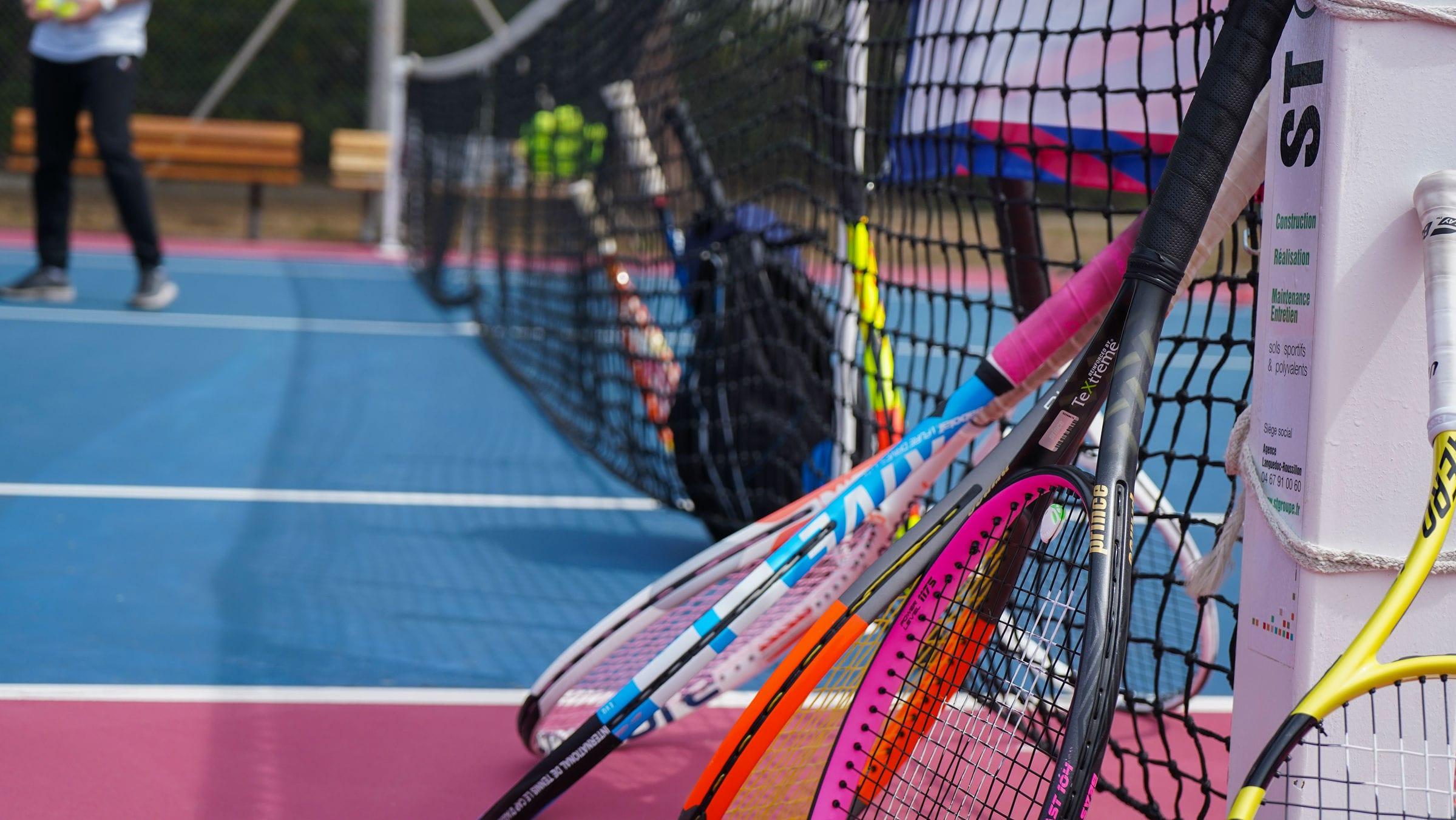 Des raquettes de tennis posés sur un filet de terrain de tennis
