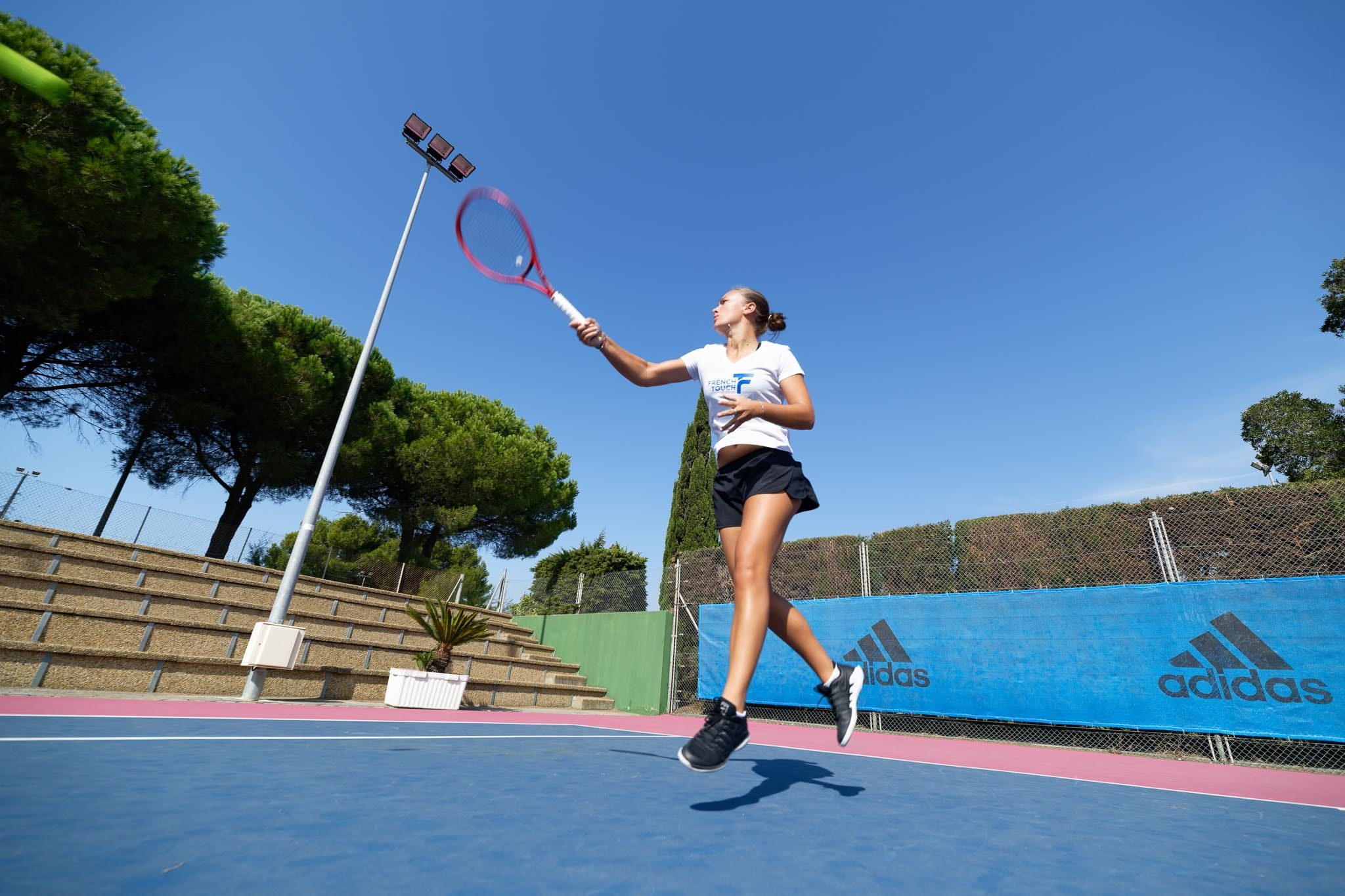 Professional tennis player training  on the center tennis court of the French Touch Academy in Cap d'Agde