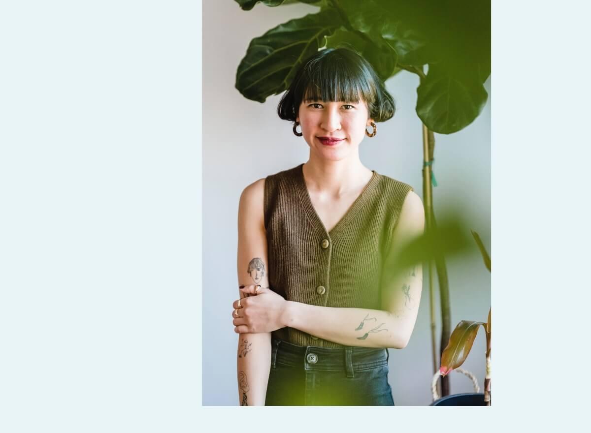 Eine junge Frau mit schwarzen Haaren lächelt und steht neben einer Zimmerpflanze.
