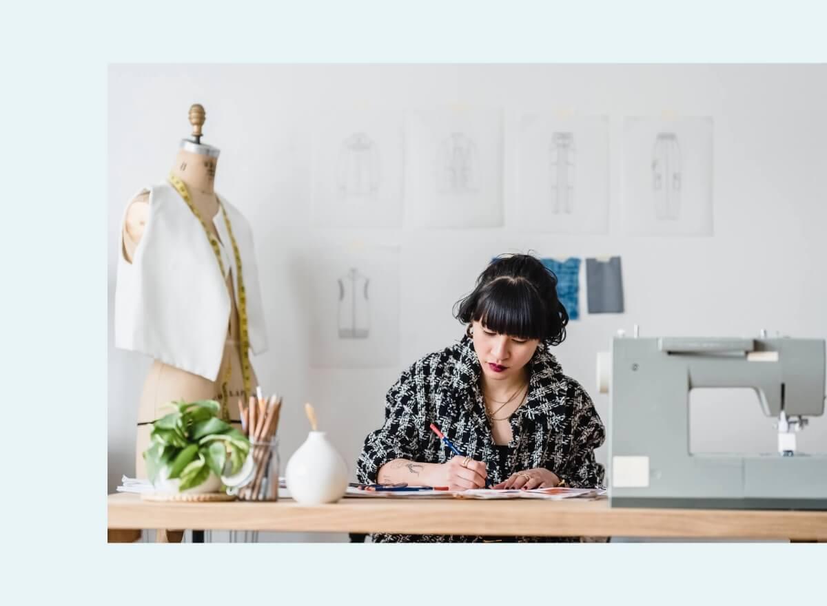 Eine junge Frau arbeitet konzentriert an Entwürfen für Kleider.