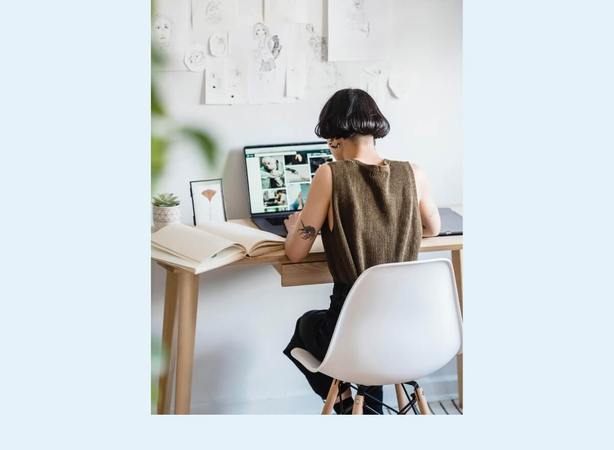 Eine junge Frau sitzt an einem Holztisch und recherchiert auf ihrem Laptop.