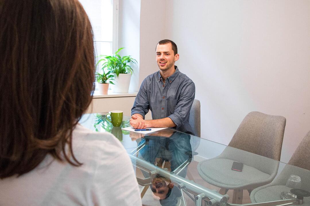 Mann am Schreibtisch im Gespräch mit Kunden.