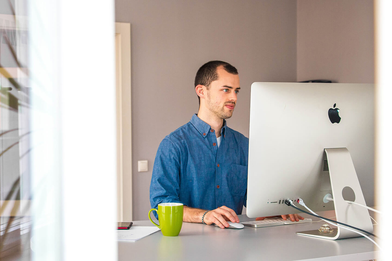 Mann arbeitet im Büro am Computer