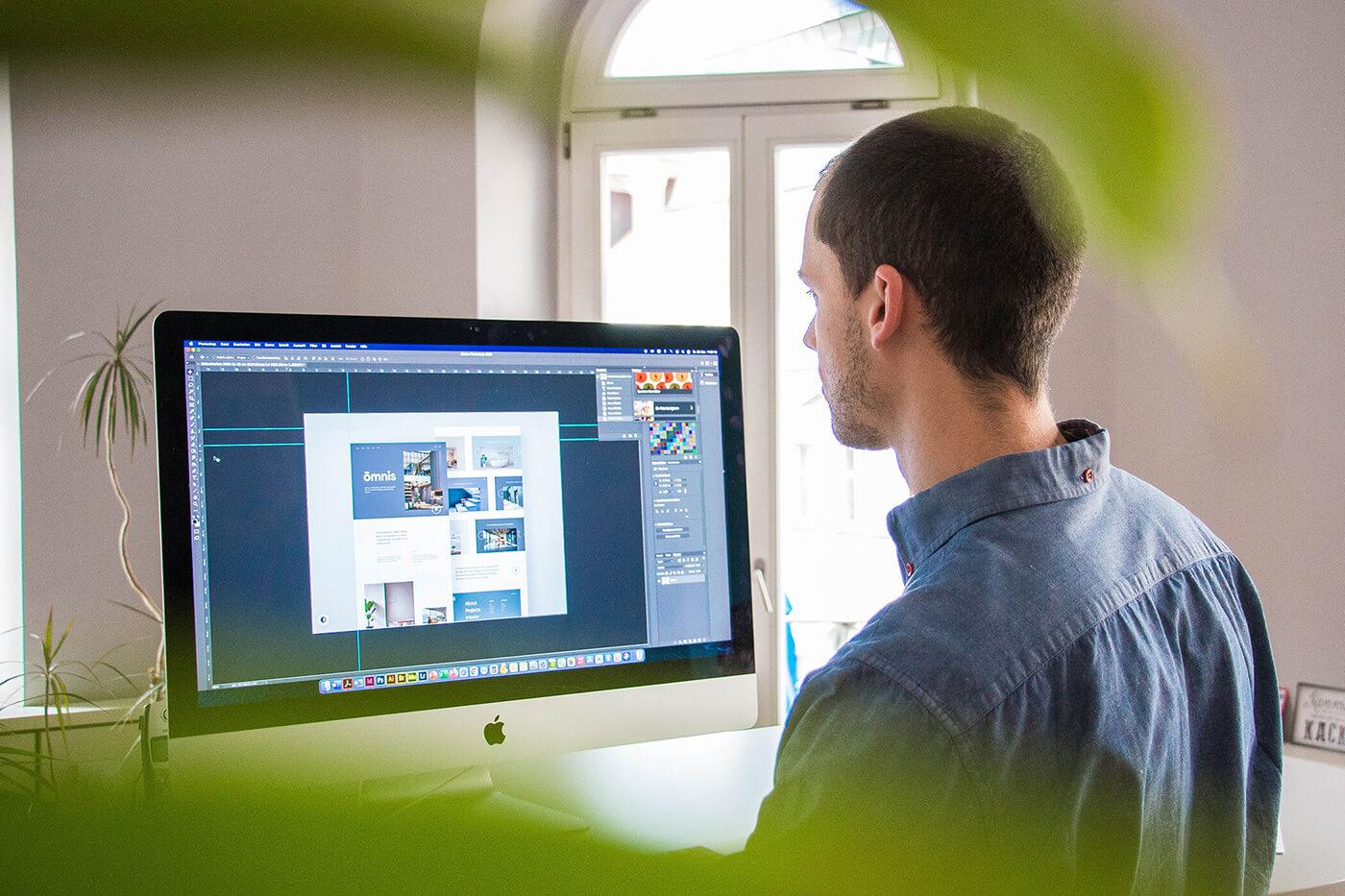 Junger Designer steht am Computer und designed.