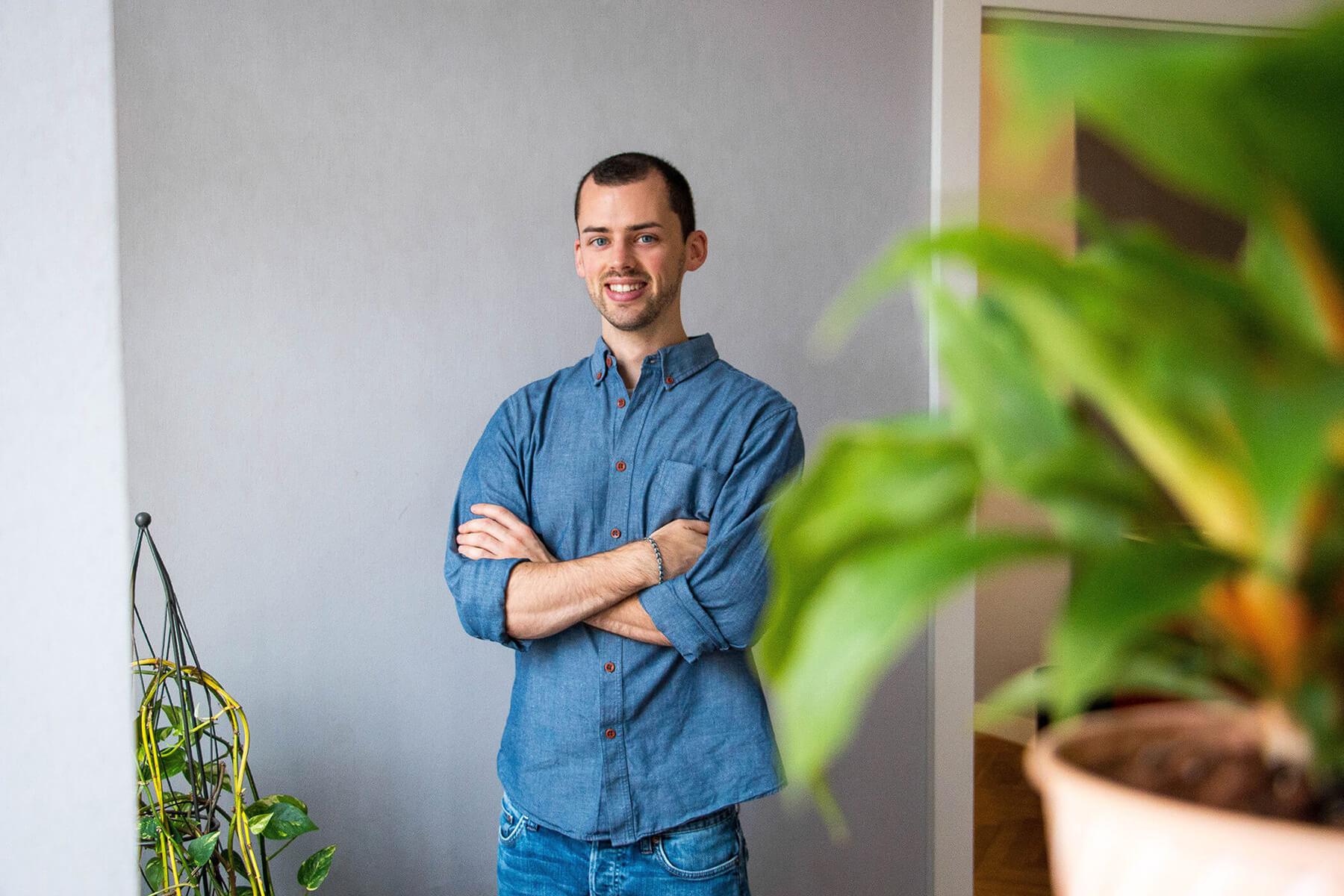 Junger Designer mit blauem Hemd steht an einer Wand und lächelt.