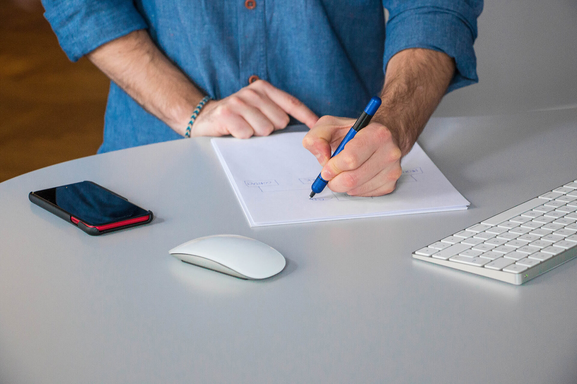 Ein junger Mann macht Notizen auf einem hellen Schreibtisch.