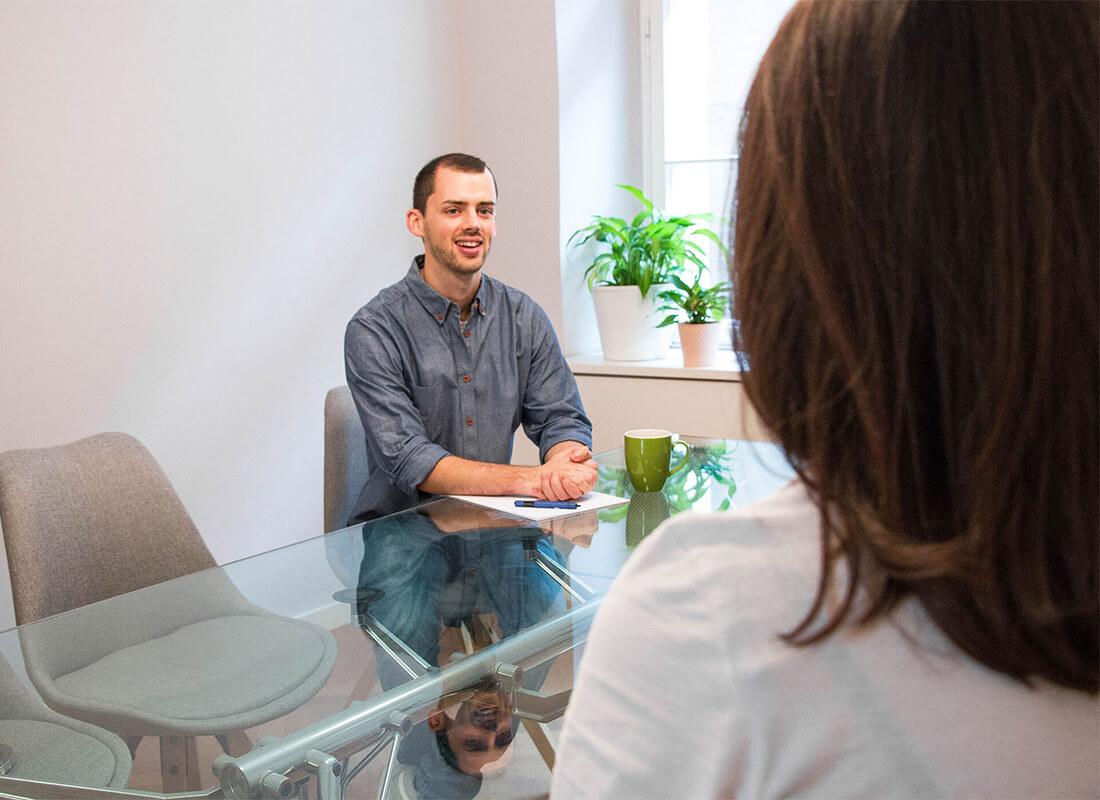 Mann sitzt am Schreibtisch im Gespräch mit Kunden.