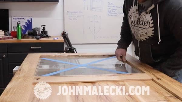 John malecki inserts glass panel into his door.