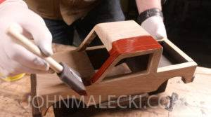 John Malecki stains wooden toy trucks with minwax wood finishes