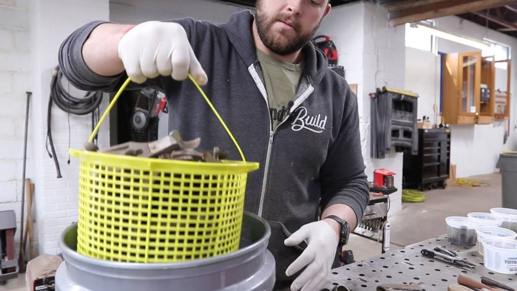 John Malecki dips old rusted tools into evapo-rust solution