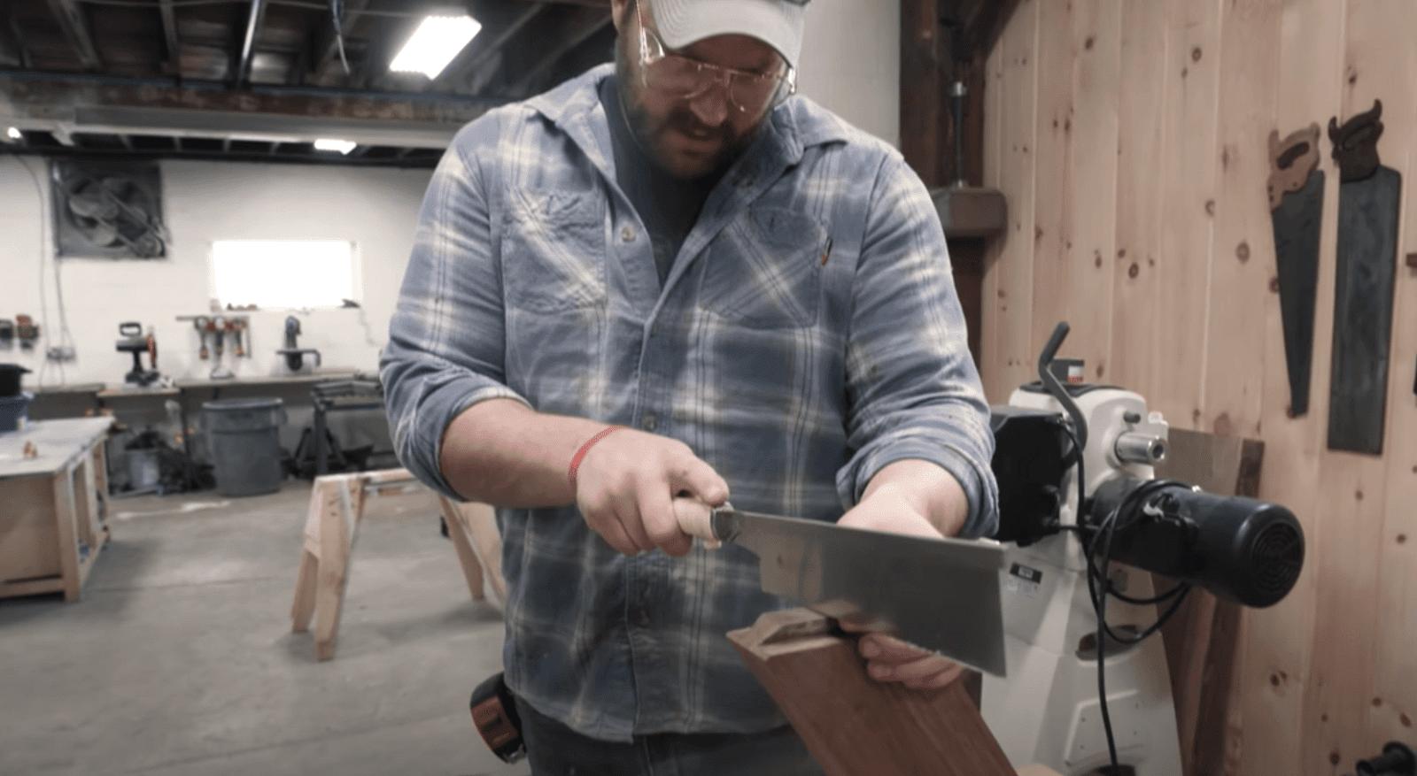John Malecki cutting the wood with saw