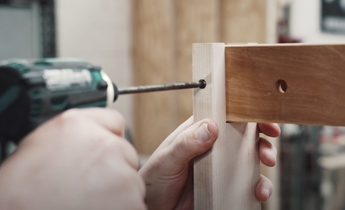 person drilling a hole into a piece of wood