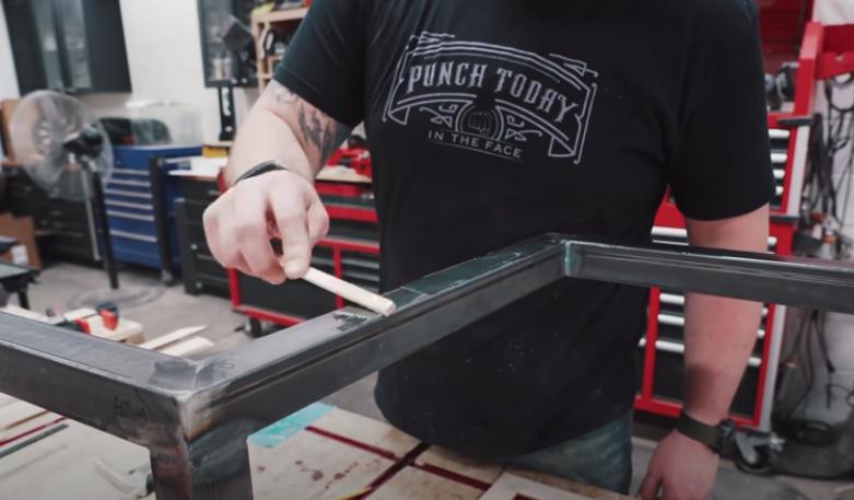 man varnishing metal