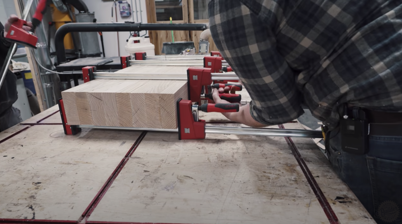 person clamping pieces of wood together