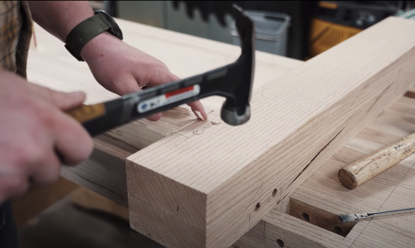 man hammering pieces of wood together