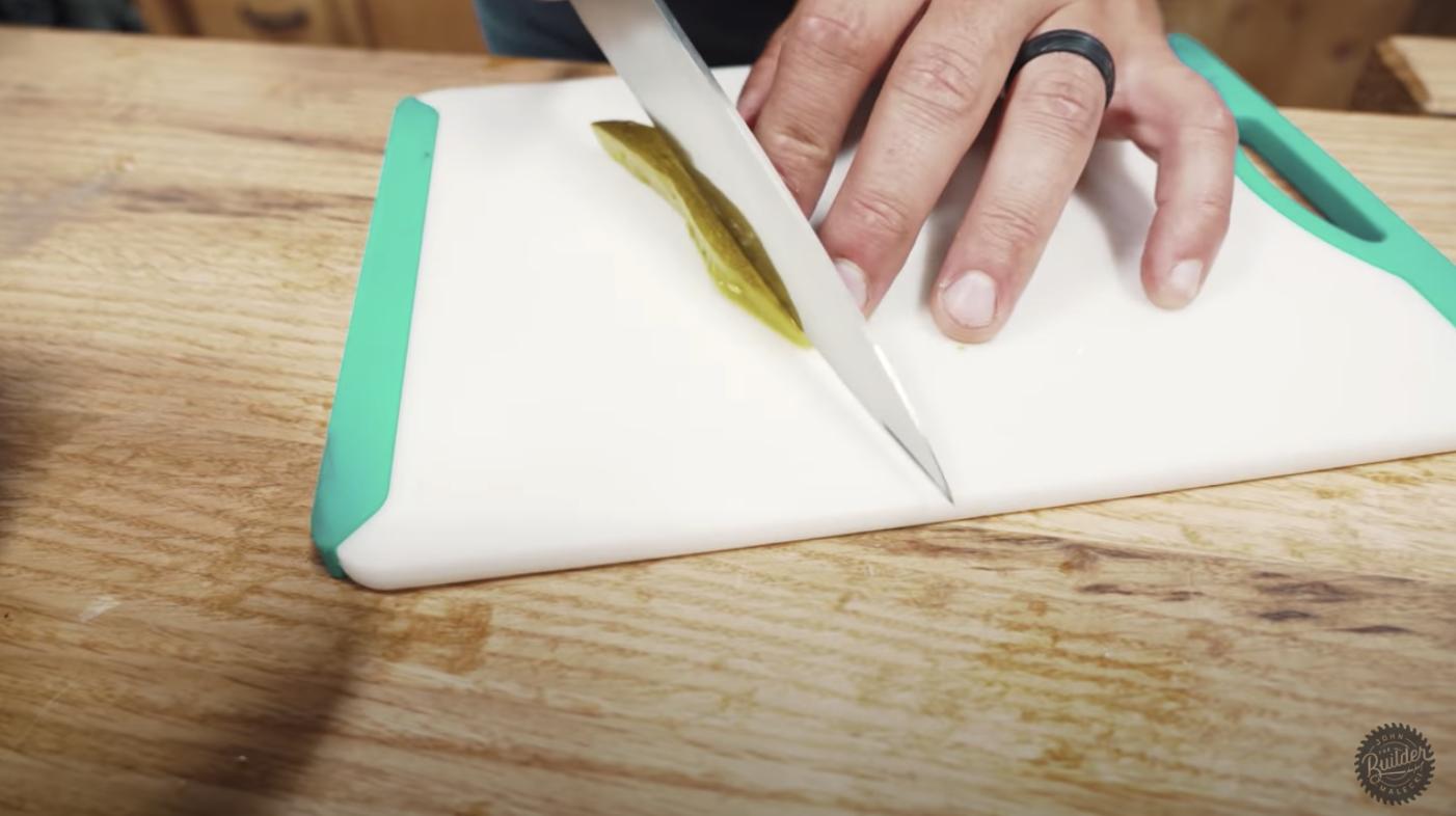 man cutting a pickle