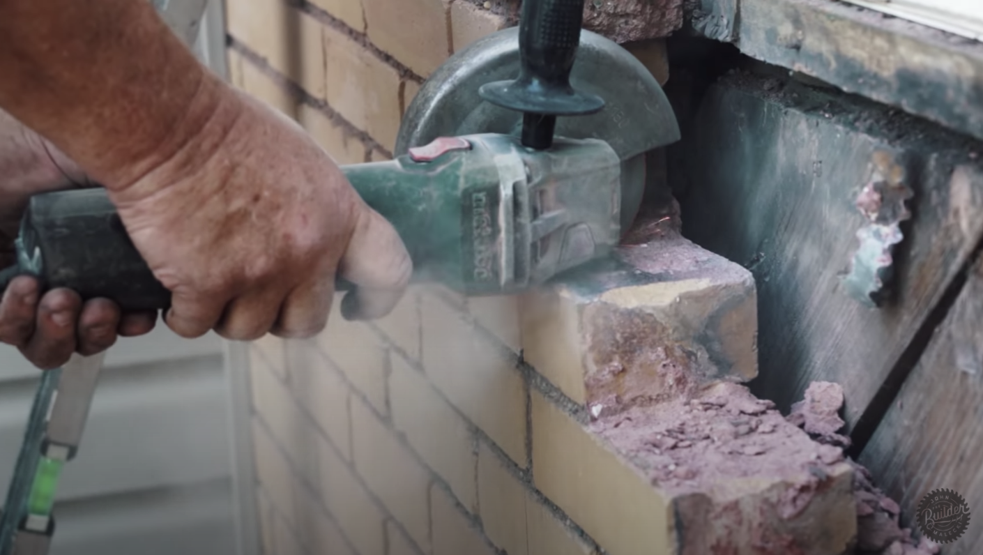 person sawing through brick