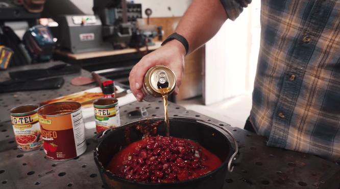 john malecki pouring beer into chili